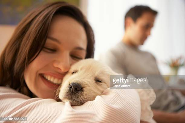 Woman holding dog, man in background, smiling