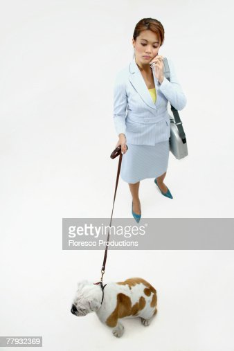 Woman holding dog on leash : Foto de stock