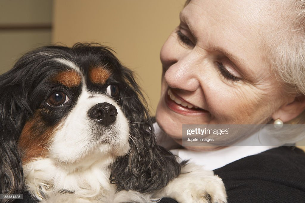 Woman holding dog : Stock Photo