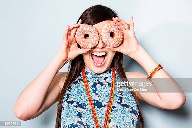Woman holding doughnuts in front of eyes.