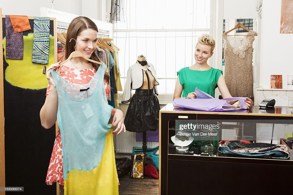 Woman holding dress in front of her.