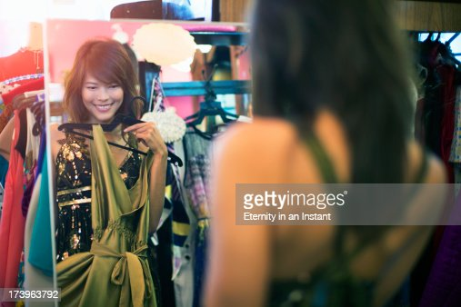 Woman holding dress in front of mirror