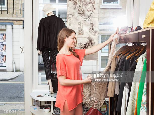 Woman holding dress up from rack in fashion shop.