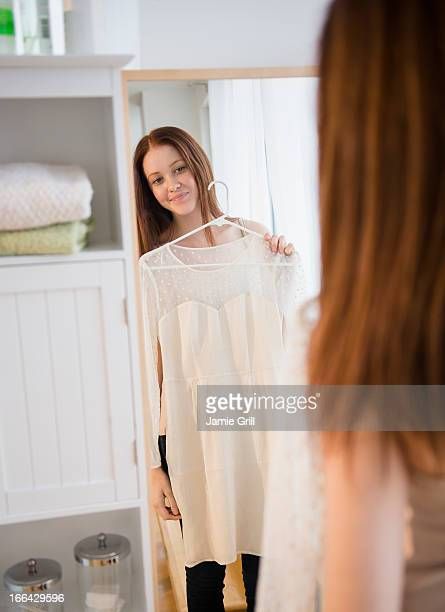 Woman holding dress up in front of mirror