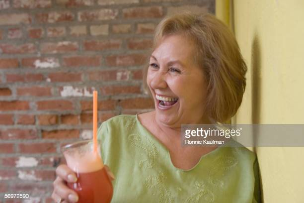 Woman holding drink and laughing