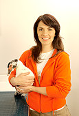 Woman holding duck in veterinary surgery, smiling, portrait