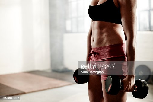 Woman holding dumbbells in gym.