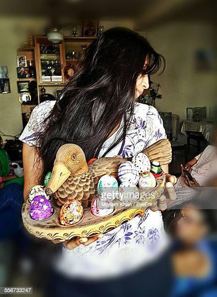 Woman Holding Easter Eggs In Wooden Plate At Home