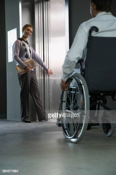 Woman holding elevator for co-worker