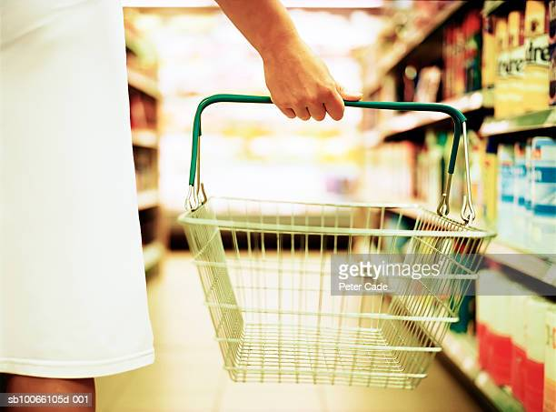 Woman holding empty basket in supermarket, mid section, close-up