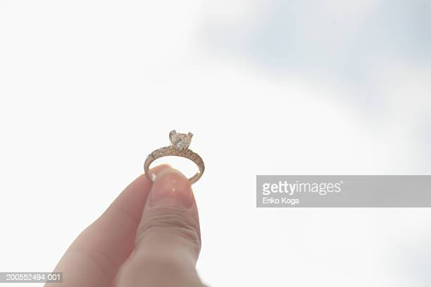 Woman holding engagement ring, focus on hands, close-up