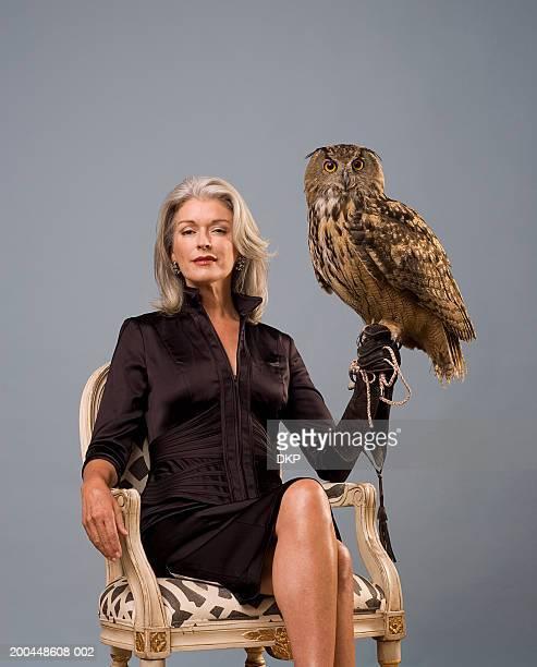 Woman holding Eurasian Eagle Owl (Bubo bubo), sitting, portrait