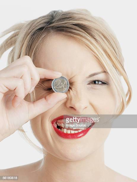 Woman holding Euro coin to her eye