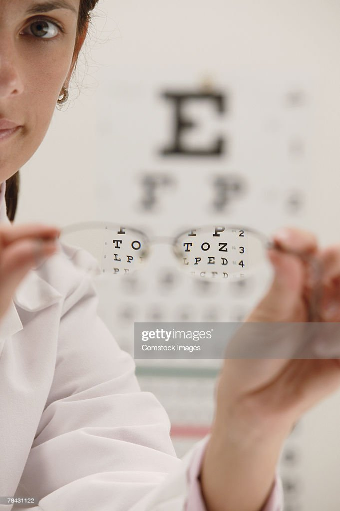Woman holding eyeglasses : Stock Photo