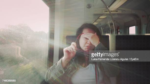 Woman Holding Eyeglasses While Traveling In Train