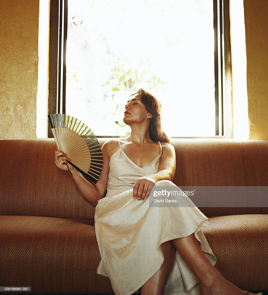 Woman holding fan on sofa : Stock Photo