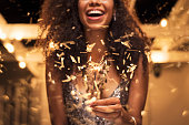 "Cheerful young woman holding single sparkler in hand outdoor. Detail of african girl celebrating new year""u2019s eve with bengal light. Closeup of beautiful woman holding a sparkling stick at party ni"