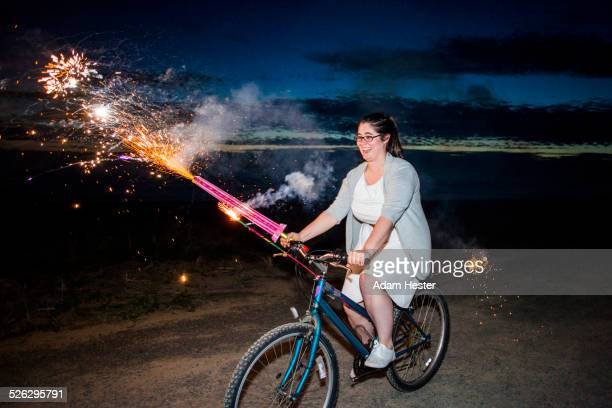 Woman holding fireworks on bicycle at night