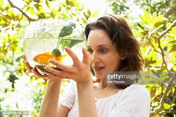 Woman holding fish bowl, smiling