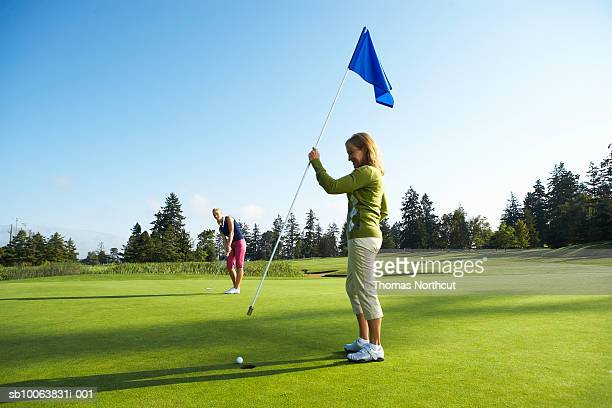 Woman holding flag, another golfer putting