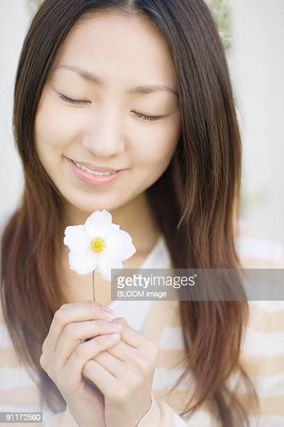Woman holding flower, eyes closed