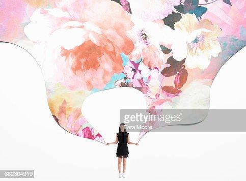 woman holding flowered wallpaper