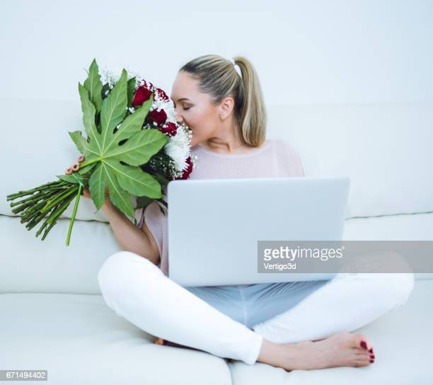Woman holding flowers and working with laptop