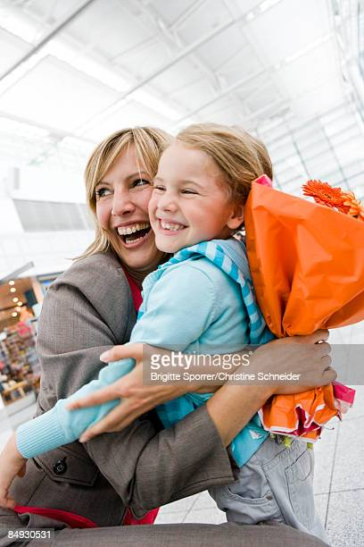 Woman holding flowers embracing girl