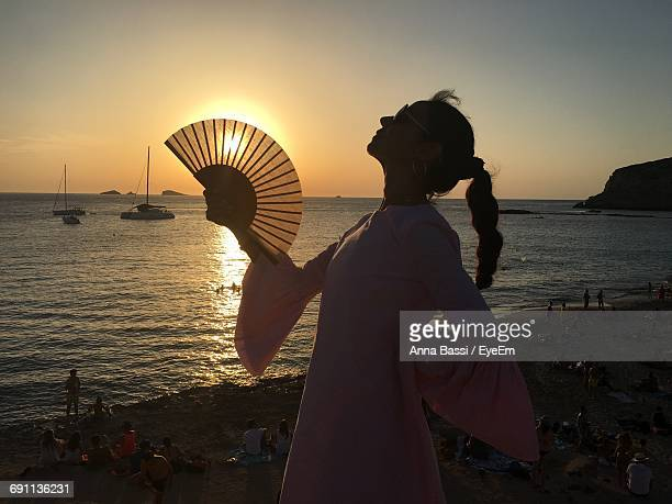 Woman Holding Folding Fan Against Sea During Sunset