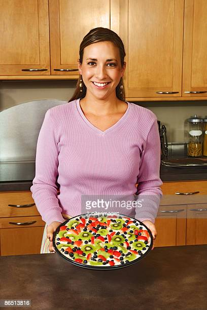 Woman holding fruit dessert in kitchen
