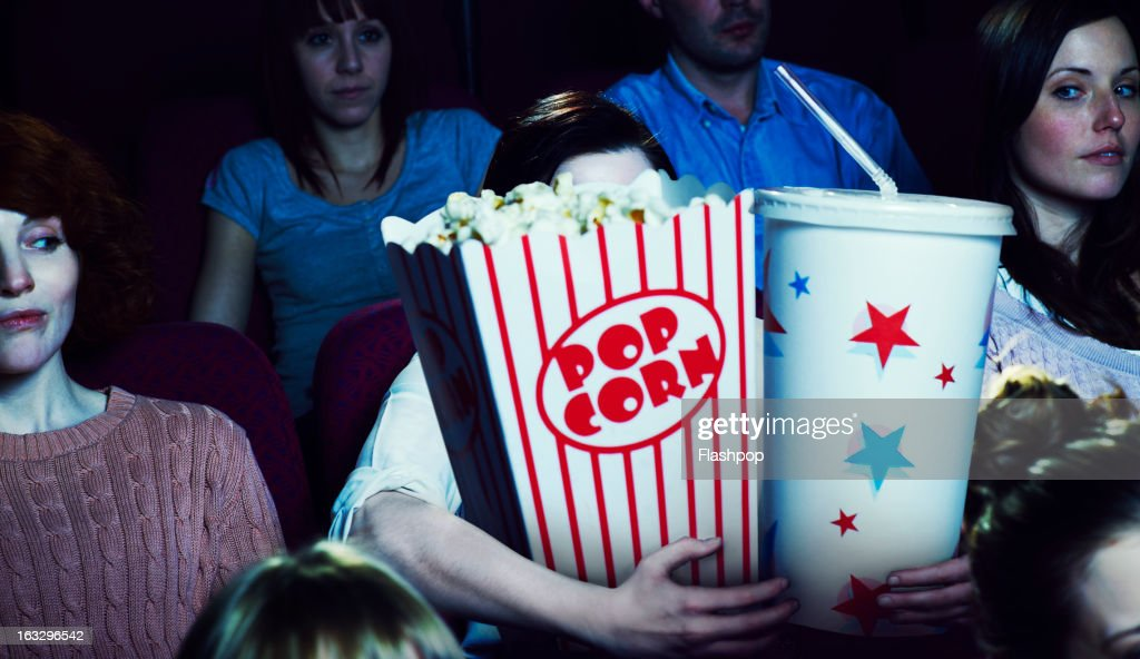Woman holding giant sized popcorn and drink
