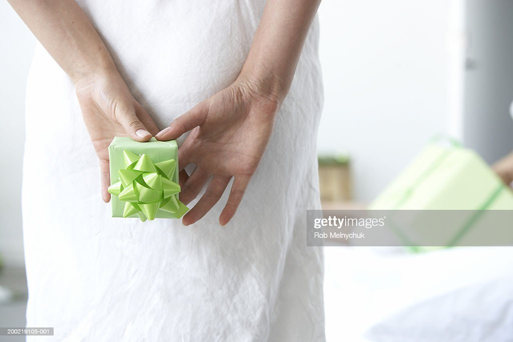 Woman holding gift behind back, mid section, rear view : Stock Photo