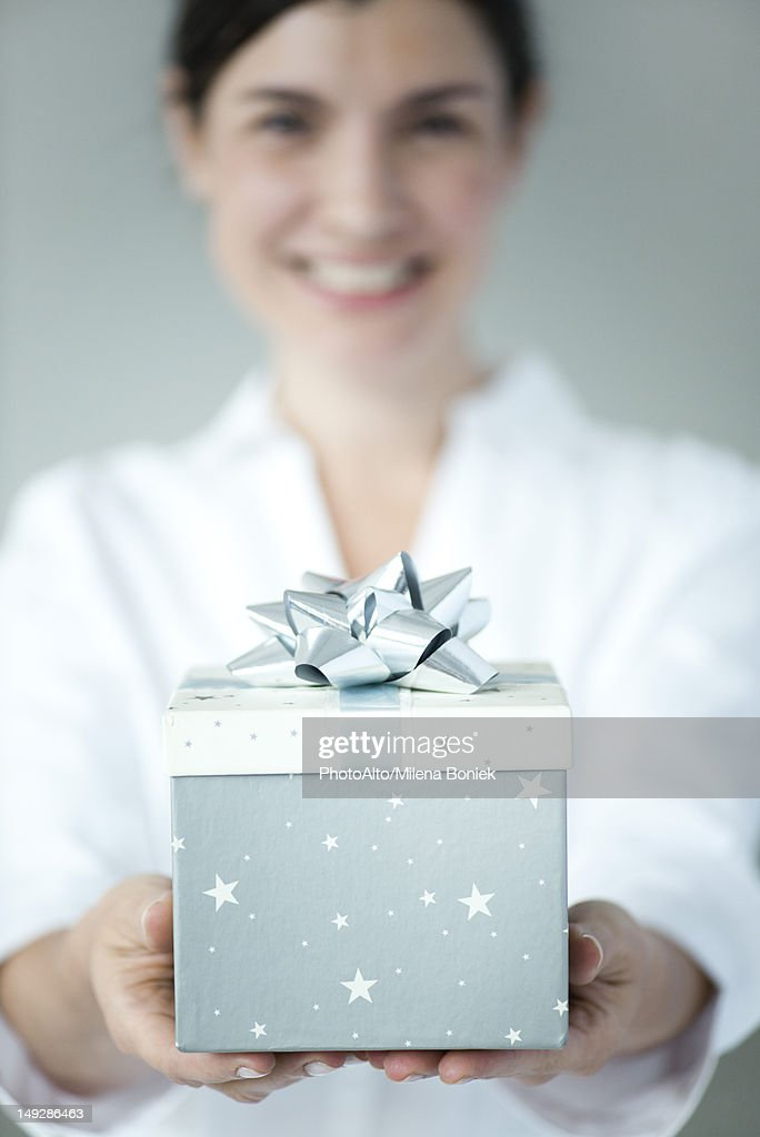 Woman holding gift box, focus on foreground : Stock Photo