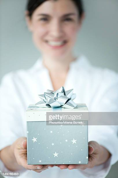 Woman holding gift box, focus on foreground