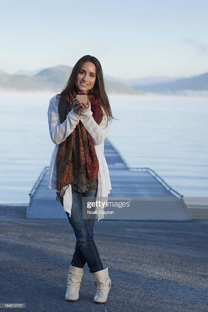 Woman holding gift by lakeside : Stock Photo