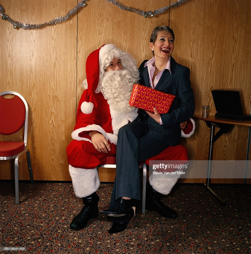 Woman holding gift, sitting on knee of man dressed as Santa