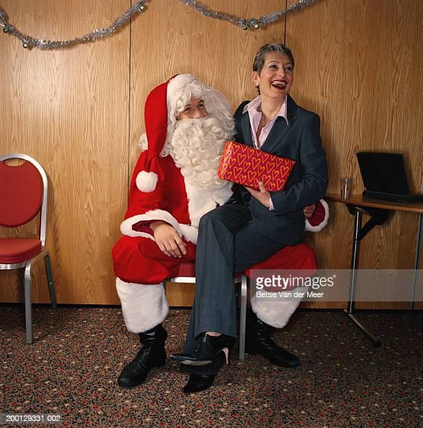 Woman holding gift, sitting on knee of man dressed as Santa