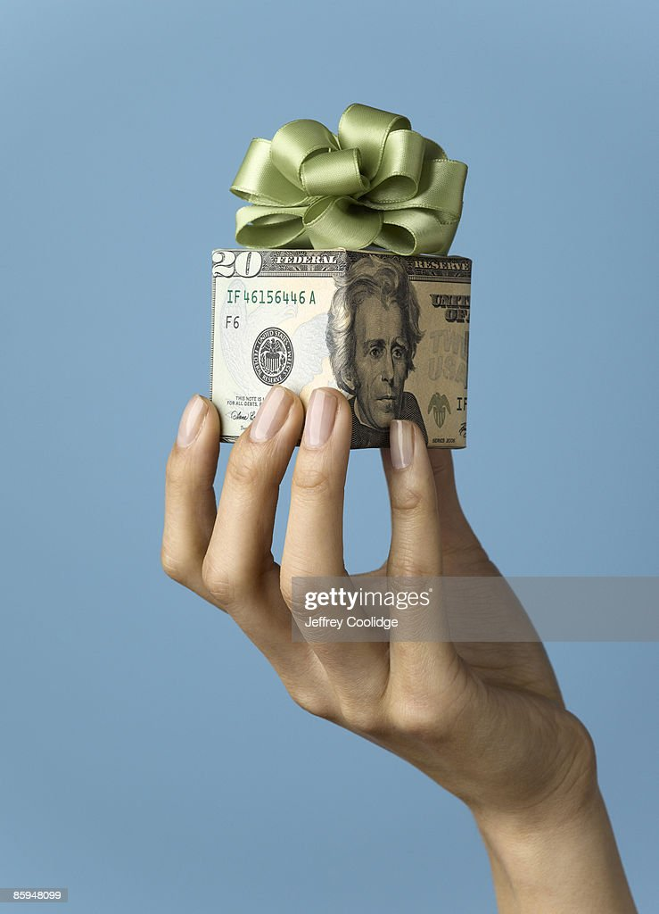 Woman Holding Gift Wrapped in US Currency : Stock Photo