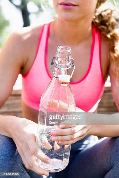 Woman holding glass bottle with mineral water
