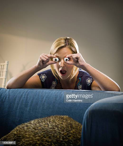 Woman holding glass eyes in living room
