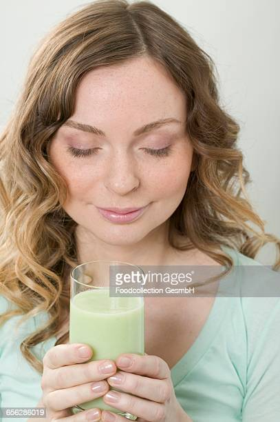 Woman holding glass of cucumber shake