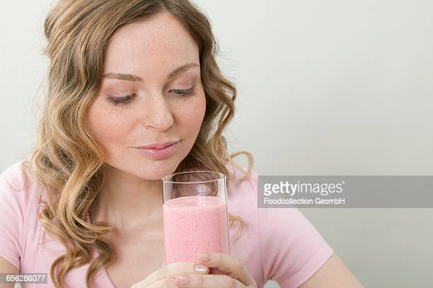 Woman holding glass of strawberry shake