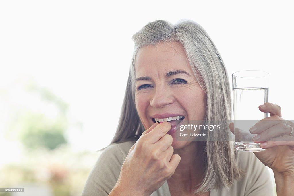 Femme tenant le verre d'eau en prenant la pilule : Photo