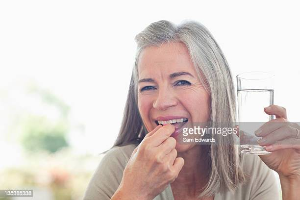 Woman holding glass of water taking pill