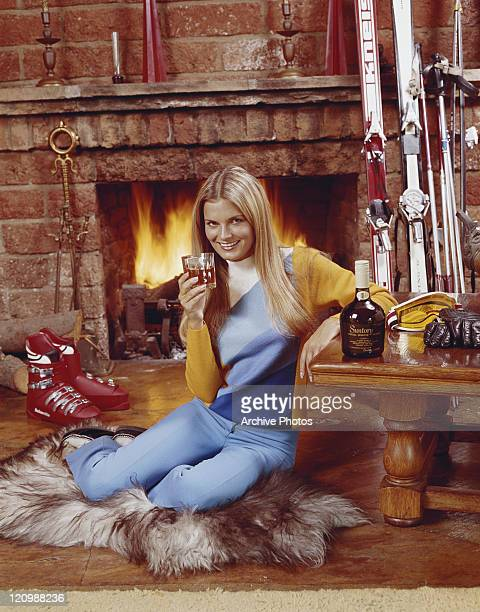 Woman holding glass of whisky sitting at fireplace, smiling, portrait