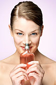 woman holding glass pump bottle up to her nose