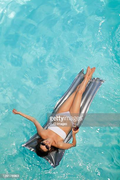 Woman holding glass while lying on raft