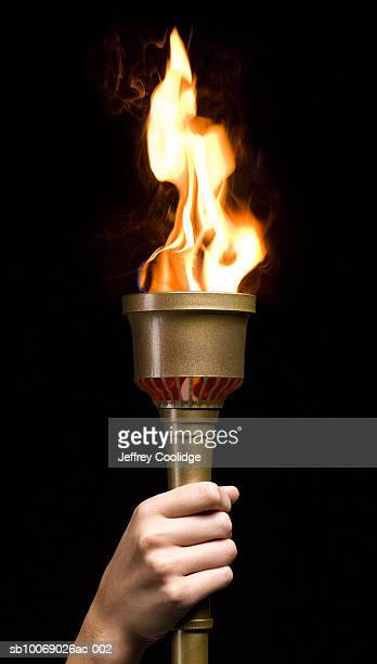 Woman holding gold torch, on black background