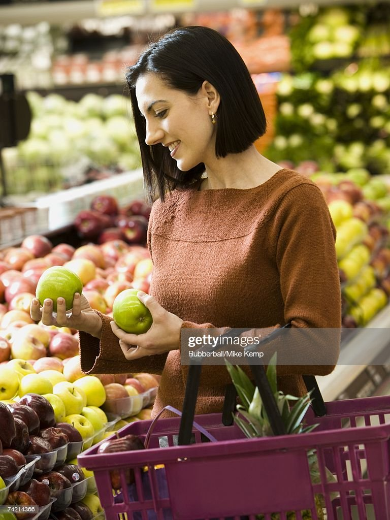 Woman holding green apples at grocery store with shopping basket : Stock Photo
