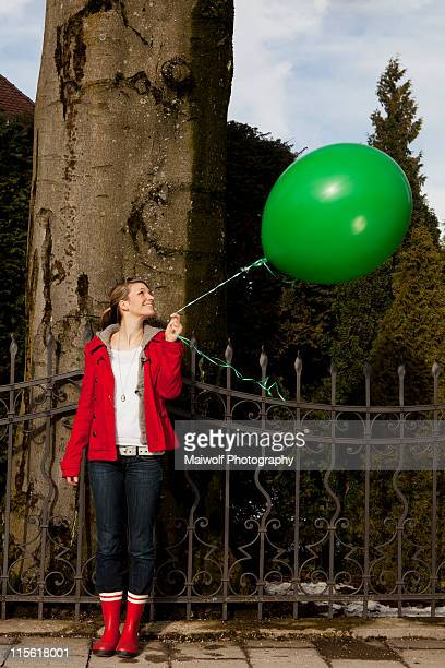 Woman holding green baloon